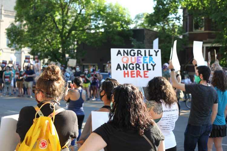 """Protester holding a sign that says """"ANGRILY QUEER, ANGRILY HERE."""""""