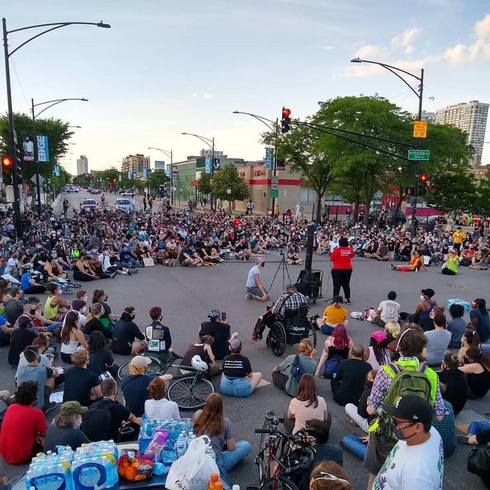 Large group of protesters seated in a circle around a speaker at a street intersection.